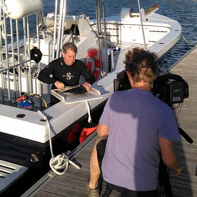 An image of a professional film crew on board a keys shark diving trip in the Florida Keys.